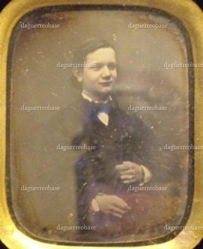 Daguerreotypi i ramme. På daguerreotypiet ses købmand Arnold Dehn (1839-1889), som ung. Rammen bærer på bagsiden et mærkat med påtrykt tekst: Georg Schou. Gl. Amagertorv No 2, KJÖBENHAVN. Med hånden er påskrevet Arnold Dehn (Manchester)