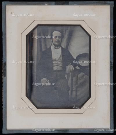 portrait of a man, sitting in a chair, leaning one arm on a table with his hat on the table, the opening of the hat is turned to the viewer! and shows a label. The man most probably is a relative of the Anthony or de Visser family. Frame is missing