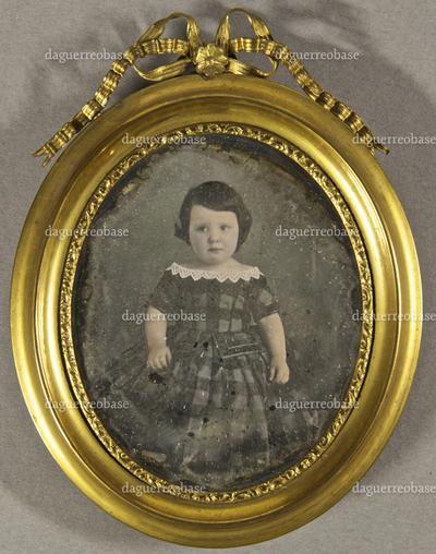 Kleines Mädchen in kariertem, schulterfreiem Kleid, stehend, Ganzfigur.