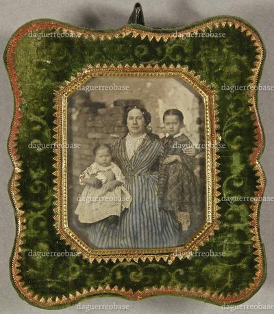 Frau mit zwei Kindern im Arm steht vor einem Stapel geschichteter Steine im Hintergrund, Dreiviertel.