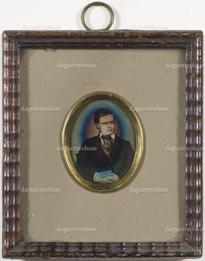 Portrait of writer Bjørnstjerne Bjørnson. A man with glasses sitting with his hands folded in his lap.