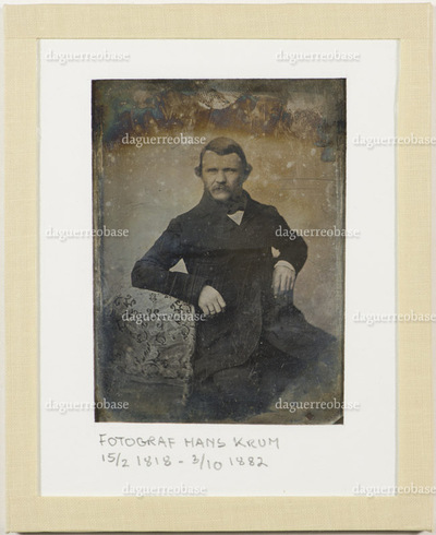 Portrait of a man previously identified as photographer Hans Krum (15.02.1818 - 03.10.1882).  He has a mustache and a ring on his finger. He is leaning on a table with a tablecloth.  The identification is uncertain.