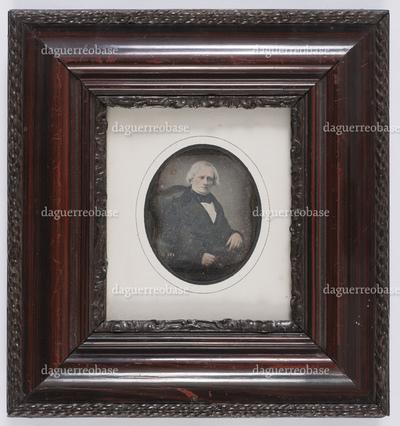 portrait en buste et de 3/4 profil d'un homme assis en studio portant des lunettes; réhaussé
