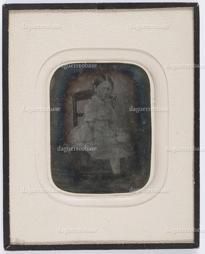portrait en pied et de 3/4 profil d'une fillette assise en studio