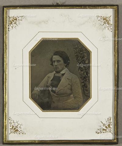Junger Mann in heller Jacke mit einem gestrickten Schal um den Hals, seitlich am Tisch sitzend, Halbfigur.
