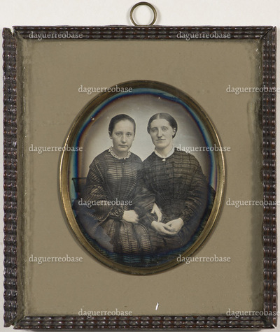 Group portrait of two women sitting. Marie Maisen Lossius (born Gram, 24.02.1839 - 24.03.1910) to the left and Marie Weyde (born Buck) to the right.  Marie has a ring on her finger.  In the inscription, a teacher named Udbye is mentioned. A guess as to who this could be is Martin Andreas Udbye (18.06.1820 - 10.01.1889), who was a singing teacher at Trondheim Katedralskole from 1852 - 1885.