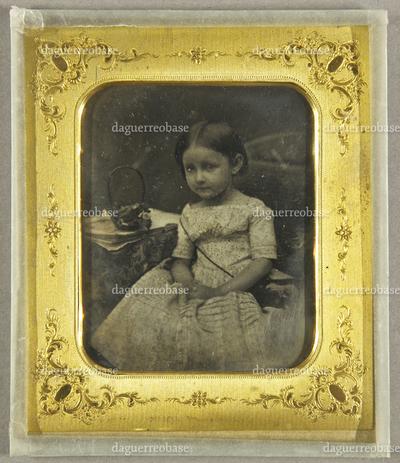 Kleines Mädchen neben einem Tisch mit einem Blumenkörbchen sitzend, Ganzfigur.