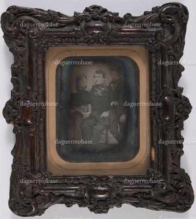 Groepsportret van 3 personen: man, zittend, jonge en meisje staand