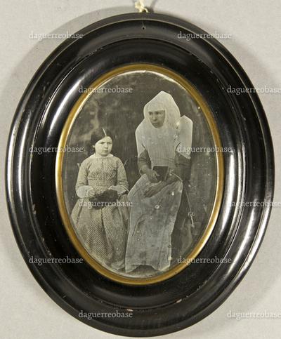 Nonne mit Gebetbuch in der Hand und einem am Gürtel befestigten Schlüsselbund. Neben ihr sitzt ein kleines Mädchen in gemustertem Kleid mit einer dunklen Tasche auf dem Schoss, Ganzfigur.