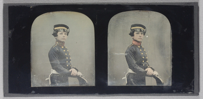 3/4 length portrait of a young boy wearing a military uniform, double breasted, looking right. His coat has brass buttons. He wears a cap with patent leather and brocade. He has a sword belt on his waist and holds gloves in his hands. Hand coloured with plain background.