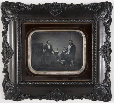 groepsportret van een man, vrouw, twee kinderen, hond, zittend aan en piano