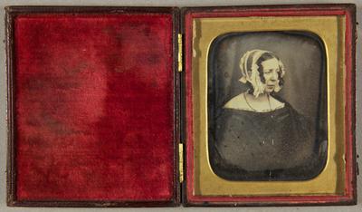 Ältere Frau mit weißer Haube in schulterfreiem dunklem Kleid und einem umgehängten Schultertuch,  seitlich sitzend, Halbfigur.