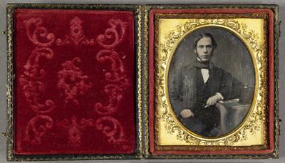 Portrait of a young man with a stereoscopic viewer and a stereo card. Puolivartalokuvassa  nuori mies. Miehellä on yllään puvuntakki, liivi ja valkoinen paita, sekä rusetti kaulassa.  Miehen oikea käsi nojaa pienen pöydän reunaan, kädessä on metallinen esine. Pöytä on peitetty liinalla. Pöydällä miehen vieressä  on stereokuva ja stereokuvien katselulaite.