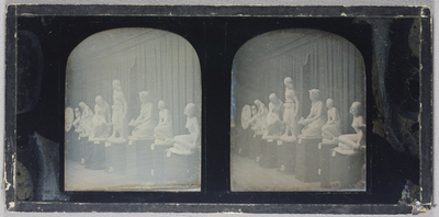 Seven statues and one relief on display in a row. Set on a wooden floor with a panelled wooden wall behind. Possibly from The Great Exhibition. Possibly in an anteroom up for removal due to the temporary labels attached to each statue.