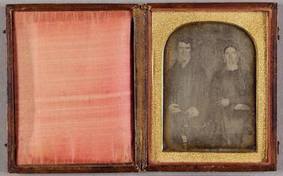 Portrait of a sitting couple. Kokokuva istuvasta miehestä ja naisesta., molemmilla on tummat asusteet. Naisella on päässä vaalean pitsireunainen hilkka. Miehellä on tummat, kiharat hiukset.