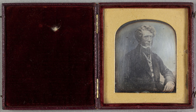 Portrait of a sitting man  with curly hair and sideburns. Puolikuva istuvasta miehestä, jolla on kihara tukka ja pulisongit. Miehellä on päällä tumma takki, liivi ja huivi kaulassa.