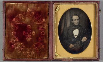 Portrait of a sitting man with a book. Puolikuva istuvasta miehestä kirja kädessään. Miehellä on suuri sillkisolmuke kaulassaan, liivistä roikkuvat kellonvitjat on väritetty kullanväriseksi.