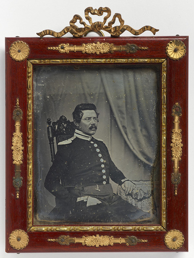 Portrait of Gustaf Edvard Tuderus in an uniform, with mustache and glasses, sitting in baroc style chair, veil on background.