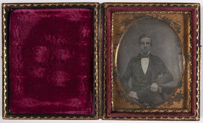 portret van een man, zittend, driekwart, frontaal, arm leunt op tafel