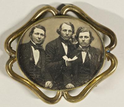 Bildnis von drei jungen Männern in einer Brosche. Der Mann in der Mitte hält ein Papier oder Brief zur Kamera, Halbfigur.