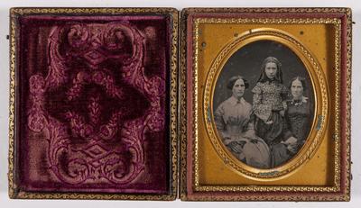 Portret van 3 vrouwen, 2 vrouwen zittend en 1 rechtop in het midden, ze leunt met haar arm op een vrouw, alle drie dragen handschoenen,