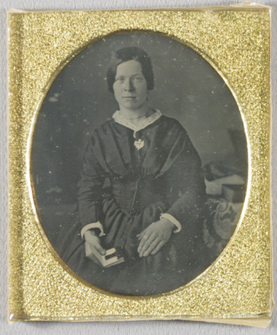 Half-length portrait of a woman in a  dark dress, facing the camera, her hands rest in her lap. she holds an open book in her left hand. She has white lace collar and white cuffs. She has a thin necklace, white brooch carved to show a thistle in blossom, and  a ring on her left hand. A table at her left elbow is covered with a cloth, another larger book rests on it.