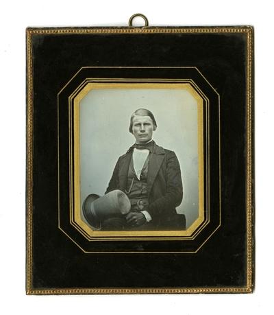 Portrett av sittende mann som holder sin hatt. Portrait of a seated man holding his hat.