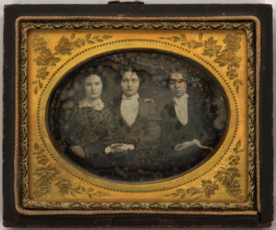 Three quarter length portrait of three young women, seated. The lady to the left wears a long sleeved patterned dress with a white lace collar. She also wears a ring and holds a book in her right hand. The lady in the middle wears a dark skirt, a long sleeved patterned jacket and a white blouse with white lace collar and a central gold brooch. The lady to the right wears a long sleeved dark dress, white blouse with a white lace collar, a central gold brooch and cuffs show beneath the sleeves. There is a fine, long chain around her neck. Their right arms rest on each other's shoulders and two ladies hold each other's hand. The image has a plain dark background.