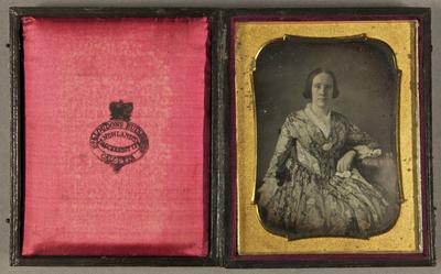 Frau in gemustertem Kleid am Tisch sitzend, auf dem ihr Arm ruht, und einem Tuch in der anderen Hand, Dreiviertelfigur.