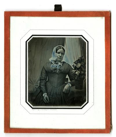 Portrett av en middelaldrende kvinne med hodeplagg. Hun sitter ved et bord med duk og en stor blomst på. Portrait of a middleaged seated woman wearing a bonnet. She is sitting by a table with a large flowering plant on.