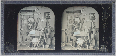 Stereo view, study of a scientist sitting in profile writing in a book. He wears a tasselled fez, long jacket, trousers, white socks and pumps (shoes). He is surrounded by equipment. Behind him is a bookcase (fake) and a round mirror, an octant on the wall, a globe beneath the table, camera on a tripod, microscopes, alembic, stereo viewer, timer, brass-bound bucket, etc.