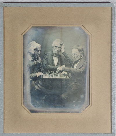 An old woman and two old men seated around a game of chess. The woman on the left wears a dress with collar, neck bow and bonnet. The man in the centre wears jacket, waist coat, shirt front and cravat with a side hair parting. The man on the right wears spectacles, jacket, shirt front and has a receding hair line.