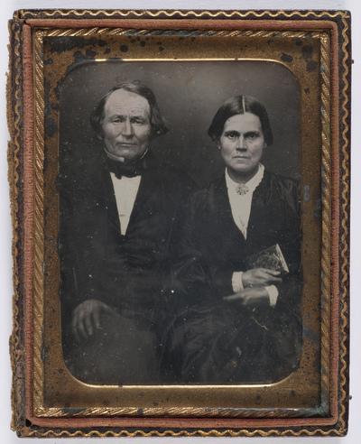 portrait en demi-hauteur d'un couple en studio, la femme tenant un petit album