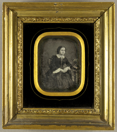 Junge Frau, dunkel gekleidet mit einem hellen Spitzenkragen, an einem Tisch mit Blumenschmuck, leicht nach vorn gebeugt sitzend, ein Arm darauf abgestützt, Dreiviertelfigur.
