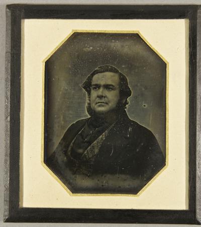 Mann mit Kinnbart, einem schwarzen Halsbinder, Brustportrait, seitlich sitzend.