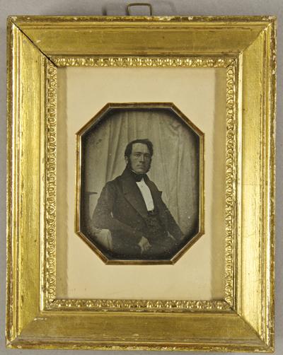 Mann seitlich neben einem Tisch sitzend, auf dem sein Zylinder steht, im Hintergrund ist ein weißes Tuch gespannt, Halbfigur.