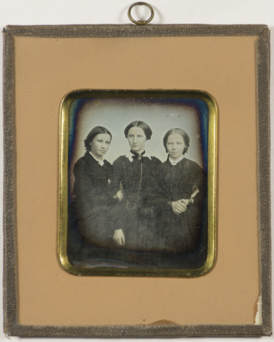 Group portrait of three young women: Mrs Nannestad, Ms Lykke Solberg and Tandberg. One has a cross as a necklace. One has a broche with what appears to be a chain on her dress.