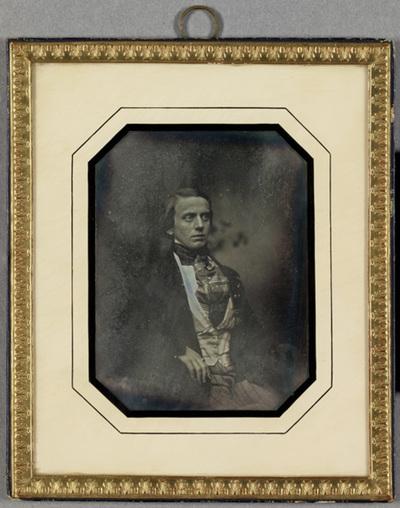 Portrait of a man who is probably a member of the Frenckell family. Puolikuva miehestä, joka on todennäköisesti Frenckellin suvun jäsen. Mies on pukeutunut tummaan puvuntakkii, raidalliseen huiviin, liiviin ja housuihin. Vasemman käden etusormessa on sormus.