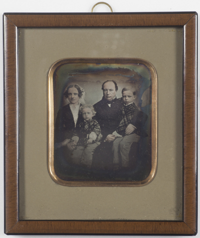 Group portrait of the family of grocer Paul Nikolai Finne (13.01.1802 - 04.11.1878) and his wife Anna Kathinka Emilie Roll. Man, woman with headwear and two children.  They had three sons, two of which are in the picture: Jakob Roll Finne (25.02.1849 -) Hans Vingaard Finne (14.01.1852 -) Paul Emil Finne (06.10.1857 -)