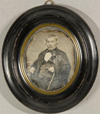 Älterer Mann mit einem Spazierstock in der Hand an einem Tisch sitzend.