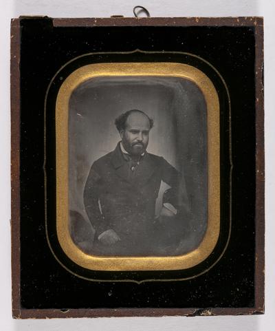Portret van een man,  kalend met baard, staand, bovenlichaam, arm steunt op stoel, lijkt hoed vast te hebben