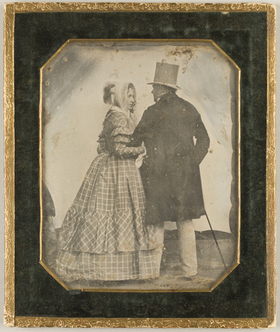 Portrait of a couple, standing with their back to us, lookinng at ech other and holding each other´s arm. The man is wearing top hat, holding a cane, the woman is wearing checked dress and a bonnet.