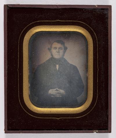 Portret van een man, bakkenbaarden, zwarte kledij, vingers in elkaar gevlochten