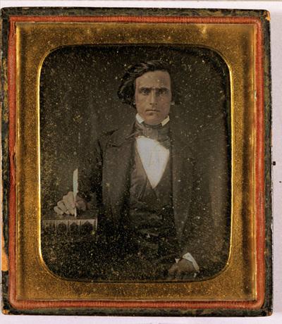 Portrait of a man with a book and pen. Puolikuva miehestä, jolla on kädessään sulkakynä ja sen alla paksu kirja.
