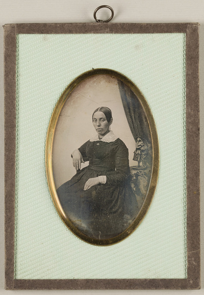Portrait od a woman seated. On the table on the right placed a little statue (woman figure). At the upper right side hanging a drapery.