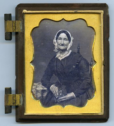 Portrait of elderly woman holding object of pearl