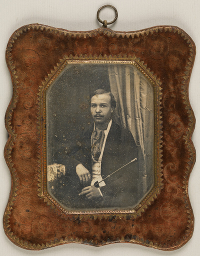 Portrait of a man with moustache, seated, holding a stick, resting his right arm on a table, wearing a polka dot neckerchief. A curtain os hanging in the back.