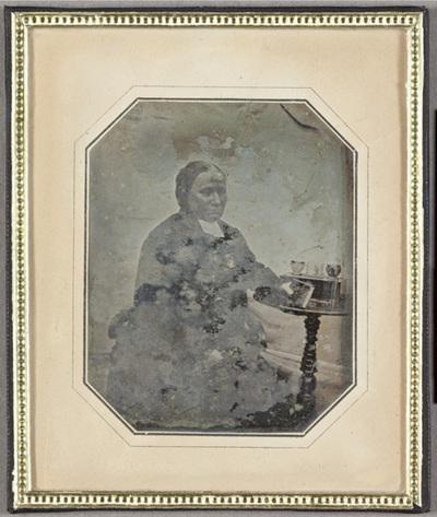 Portrait of a man with a book, table on the right side with glass objects. Puolikuvassa istuva mies, jonka oikealla puolella on pieni pöytä, jolla on esineitä. Miehen kädessä on kirja.