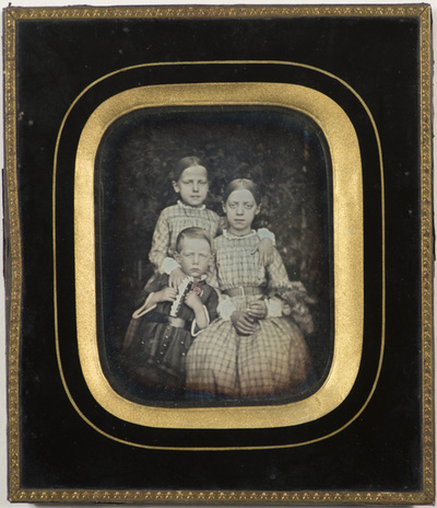 Group portrait of three children who are siblings. Fredrikke Marie Gram (married Qvam), Ingeborg Henrikke Gram (married Bergh), engineer Jakob Schavland Gram.  Fredrikke Marie is holding what appears to be flowers.  A broche or flower on Jakobs chest has been hand-coloured with red.
