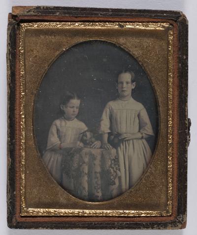 portrait en demi-hauteur de 2 fillettes en studio, appuyées à une table; réhaussées